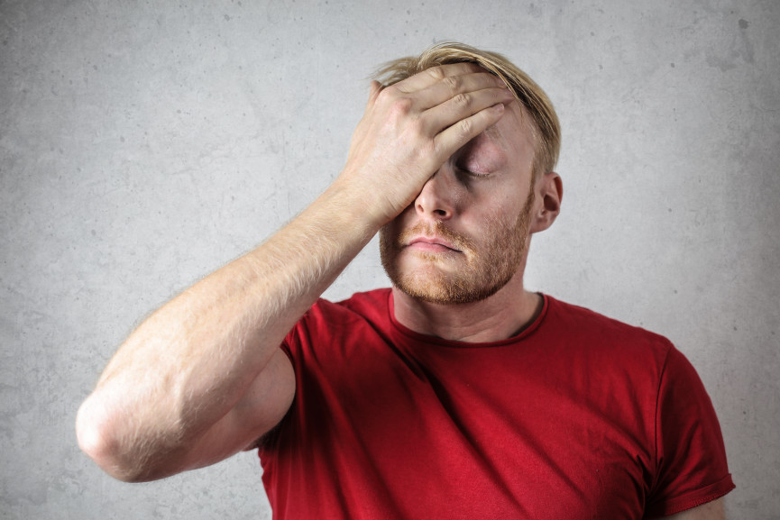 Canva - A Man in Red Shirt Covering His Face